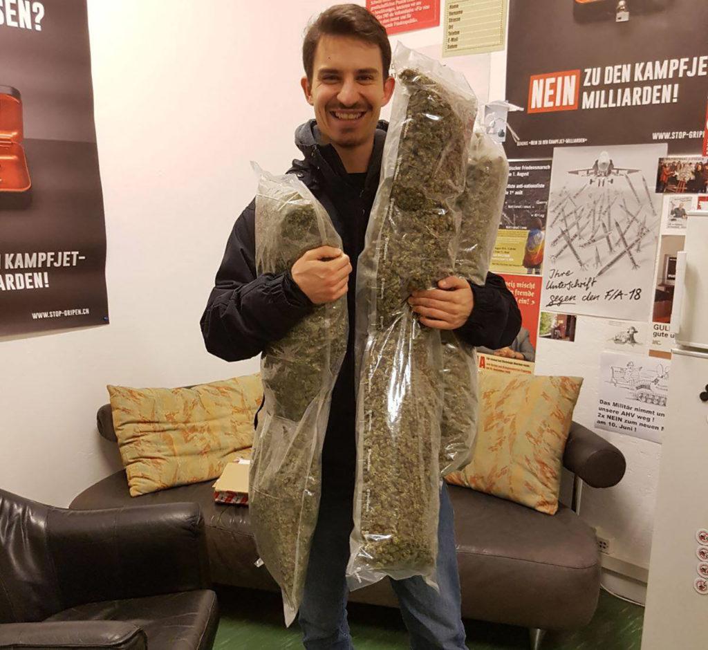Een foto van Nino Forrer, persvoorlichter van de Zwitserse 'Legalize It!'-beweging. Hij staat in een kleine kamer voor een bank en stoel, met politieke affiches aan de muur. Hij glimlacht en houdt drie enorm grote zakken met cannabisbloemen vast.