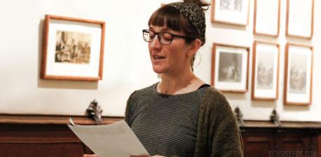 La fotografía muestra la imagen de la activista procannabis Patty Amiguet. Sujeta varias hojas de papel en la mano y parece estar leyéndolas en voz alta. Patty lleva gafas y un pañuelo atado alrededor de la cabeza. En la pared, a su espalda, vemos fotografías antiguas en tonos sepia enmarcadas.