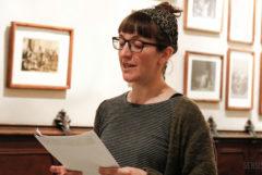 La photo montre la militante pro-cannabis Patty Amiguet. Patty tient quelques feuilles de papier et semble en lire le contenu à haute voix. Elle porte des lunettes et une écharpe pour retenir ses cheveux. Des cadres contenant de vieilles photos en sépia sont accrochés au mur derrière elle.