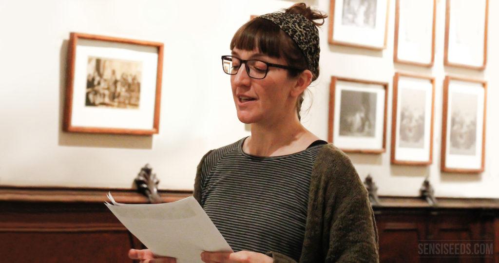 Auf dem Foto ist die Cannabisaktivistin Patty Amiguet zu sehen. Sie hält ein paar Blätter Papier in der Hand und scheint davon vorzulesen. Patty trägt eine Brille und ein Tuch im Haar. An der Wand im Hintergrund hängen historische, braun gerahmte Bilder.