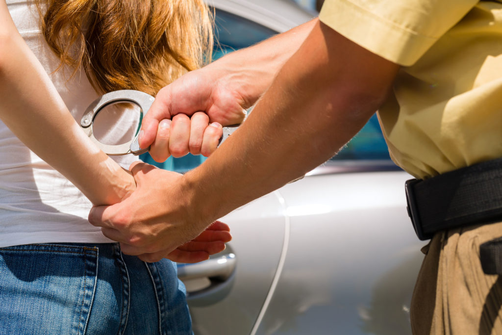 In the photo, a man is handcuffing a woman. The sun is shining, and they are both standing in front of a silver car. The woman has long brown hair. She is wearing blue jeans and a white shirt. The man is wearing brown trousers, a broad belt and a loose mustard-coloured shirt. This could be the uniform of a German policeman. Because the photo is taken in close-up, only the arms of the two people can be seen clearly.