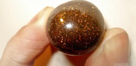Gros plan d'un morceau de haschich brun roulé en boule. Pour la photo, quelqu'un tient le haschich entre le pouce et l'index gauches.