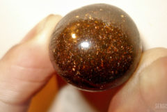 Close-up of a piece of brown hashish that has been rolled into a ball. Someone is holding the hashish up to the camera between their left thumb and forefinger