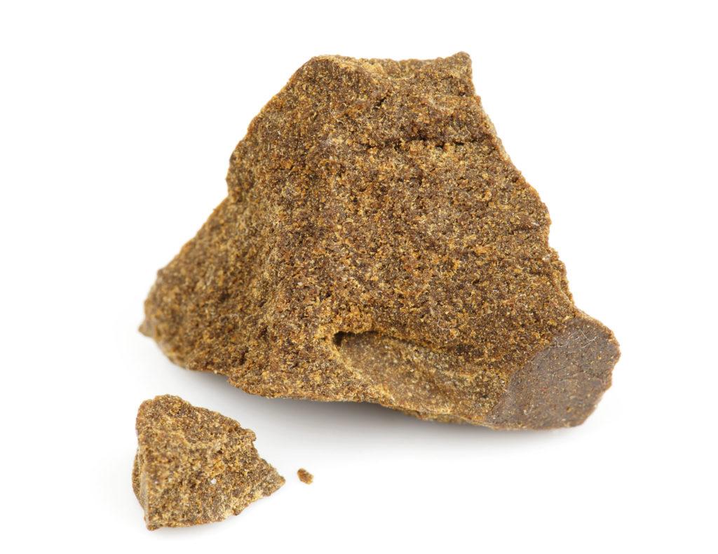 Primer plano de dos trozos de hachís marrón elaborados a partir de kief.