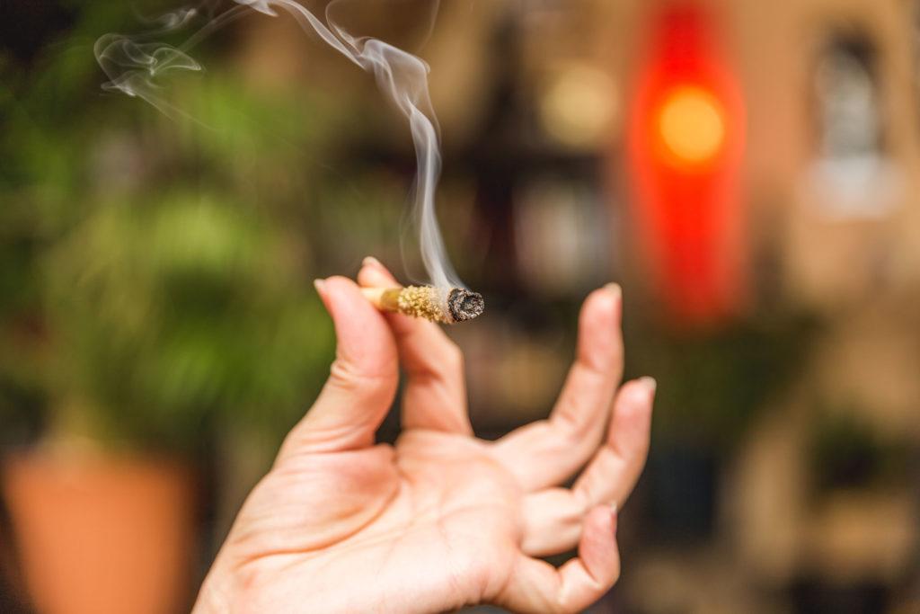 Foto einer Frauenhand, die einen mit Kief bestreuten, brennenden Joint in die Kamera hält.