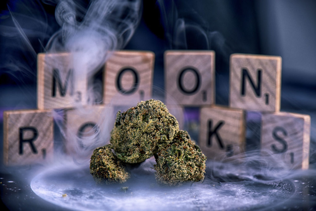 "The photo has three cannabis buds in the foreground. They are surrounded by smoke. In the background are some Scrabble letters spelling the word ""Moonrocks""."