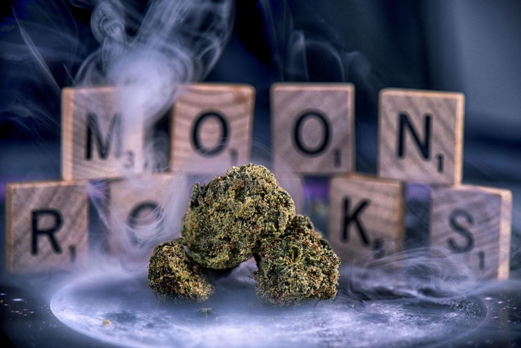 Trois buds de cannabis entourés de fumée apparaissent à l'avant-plan. À l'arrière-plan, des lettres de Scrabble constituent le mot « Moonrocks ».