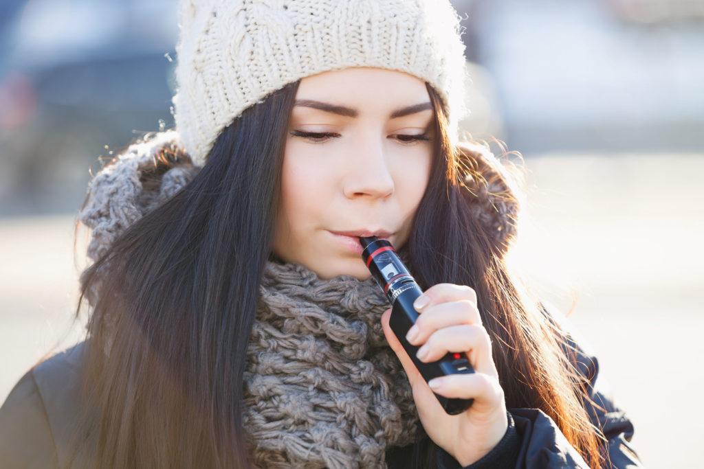 Foto retrato de una mujer joven que lleva una gorra y una bufanda, y que está inhalando de un gran cigarrillo electrónico.