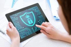 Fotografía de una mujer que sostiene una tablet en las manos. En la pantalla se muestran un candado y una hoja de cannabis.
