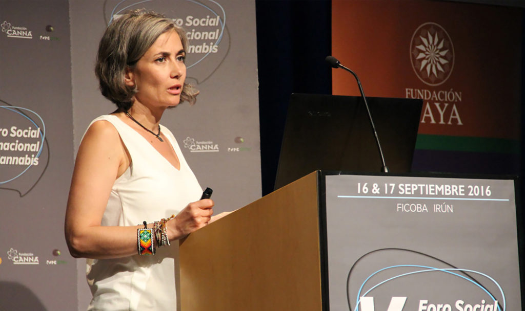 "Photo of Dr Cristina Sanchez, standing at a speaker's lectern. On this you can see ""16 & 17 September 2016, Ficoba, Irun"". Dr Sanchez is wearing a sleeveless shirt, coloured bracelets, a chain and styled chin-length hair."