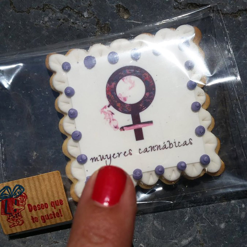 "In the photo you can see an edible that is packaged in a small clear plastic box. On the square white edible there is a Venus symbol and below that the name ""mujeres cannábicas"" (cannabis women). The photo also depicts a finger with red nail polish pointing at the edible."