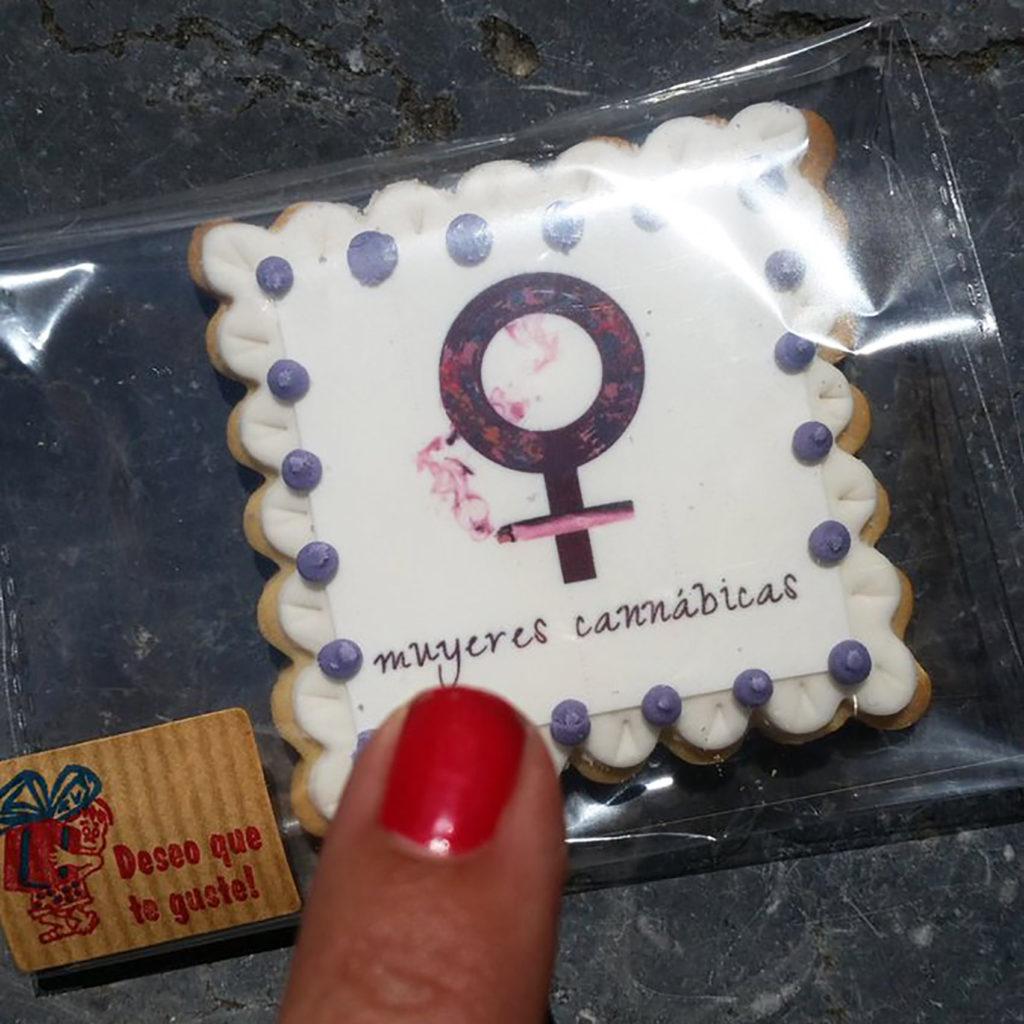 """Op de foto zie je een edible verpakt in een klein, doorzichting plastic doosje. Op de vierkante, witte edible staat een Venus-symbool met daaronder de naam """"mujeres cannábicas"""" (cannabisvrouwen). Op de foto zie je ook een vinger met een rood gelakte nagel die naar de edible wijst."""