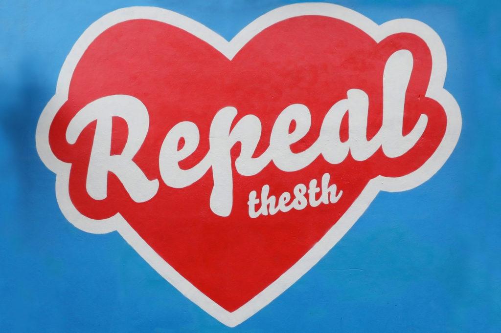 Comment la campagne d'abrogation l'a-t-elle remporté ? En plus d'annuler l'interdiction forçant les Irlandaises à voyager outre-mer pour obtenir des services d'avortement, le mouvement pour abroger le huitième amendement, dit campagne d'abrogation, a révélé un nouveau type de militantisme civique en Irlande : un militantisme disposé à collaborer avec la classe politique tout en refusant de tolérer davantage les injustices d'une loi dépassée. Cela a démontré que lorsque la cause le mérite, la nation peut dynamiser son argumentation en parlant d'une seule voix, une voix qui détient le pouvoir de faire évoluer les mentalités, la règlementation et l'histoire. C'est une série d'événements majeurs pendant la campagne qui a fait basculer l'opinion publique en faveur de l'abrogation, le premier étant la mort de Savita Halappanavar. Savita faisait une fausse couche à sa 17e semaine de grossesse quand elle est arrivée à l'hôpital universitaire de Galway en 2012. Sa demande d'arrêt de grossesse lui a été refusée ; trois jours plus tard, elle décédait. La nouvelle de son décès évitable a soulevé un tollé général si puissant que Savita est devenue l'improbable héroïne de la campagne d'abrogation, qui du même coup, a pris un nouvel élan. Quand l'humoriste Tara Flynn a parlé publiquement de son avortement en 2015, suivie de Roisin Ingle, éditrice du Irish Times, des milliers de femmes partout en Irlande se sont soudainement senties représentées par les médias irlandais et ont commencé à prendre la parole. Les comptes Twitter et les sites internet ont offert des plateformes aux expériences jusque-là passées sous silence. À la radio, sur les médias sociaux et sur les seuils de porte, les gens échangeaient des histoires à propos de décisions médicales difficiles, puis en 2016, il est devenu évident que ça ne s'arrêterait pas. Pressé de montrer les progrès réalisés, le gouvernement a annoncé qu'il tiendrait une assemblée citoyenne en 2017. Au moment où l'assemblée publiait ses conclus