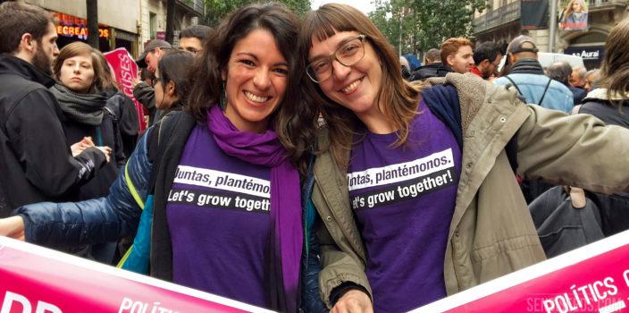 """En la fotografía se ve a la activista procannabis Patty Amiguet (a la derecha) y a otra mujer (a la izquierda). Están en una manifestación Sonríen a la cámara y llevan camisetas de color morado con el lema """"Let's grow together!"""" (Juntas, plantémonos)."""