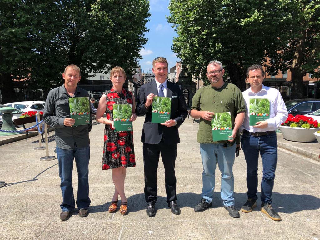 Foto auf dem Gino Kenny, Vera Twomey, Niall Neligan, Kenny Tynan und Garret McGovern zu sehen sind. Sie halten eine Broschüre mit einem Cannabisblatt in die Kamera.