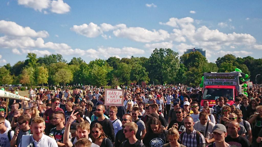 Een foto van de Hennepparade 2018 in Berlijn, waarop voornamelijk jonge, mannelijke demonstranten te zien zijn. Een demonstrant houdt een bord omhoog waarop staat 'Hemp has a future'.
