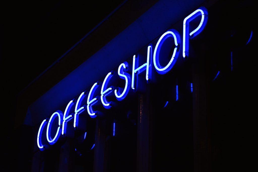 """Fotografía de unas luces azules de neón formando la palabra """"coffee shop""""."""