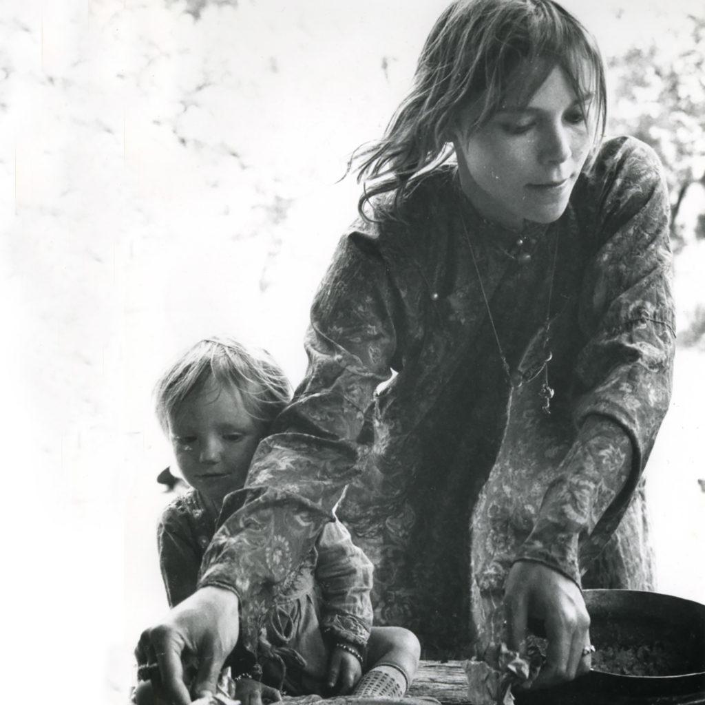 Foto auf dem Mila Jansen und ihre Tochter Miloes abgebildet sind. Mila ist beschäftigt mit Kochen, Miloes schaut ihr schüchtern zu. Beide tragen weite, dünne Kleider. Das Foto wurde 1968 in der nordindischen Stadt Manali aufgenommen.
