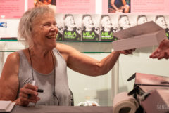 Photograph of a laughing Mila Jansen signing copies of her autobiography Mila: How I Became the Hash Queen during its presentation at the Hash Marihuana & Hemp Museum. In front of Mila is a champagne glass, and in the background several copies of her autobiography are visible.