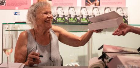 Fotografía de una sonriente Mila Jansen firmando copias de su autobiografía Mila: How I Became the Hash Queen (Mila: cómo me convertí en la reina del hachís) durante la presentación del libro en el Hash Marihuana & Hemp Museum. Delante de Mila hay una copa de champán y, al fondo, se ven varios ejemplares de su autobiografía.