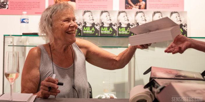 Een foto van een lachende Mila Jansen die exemplaren van haar autobiografie Mila: How I Became the Hash Queen signeert tijdens de presentatie van het boek in het Hash Marihuana & Hemp Museum. Voor Mila staat een champagneglas en op de achtergrond zijn een aantal exemplaren van haar autobiografie te zien.