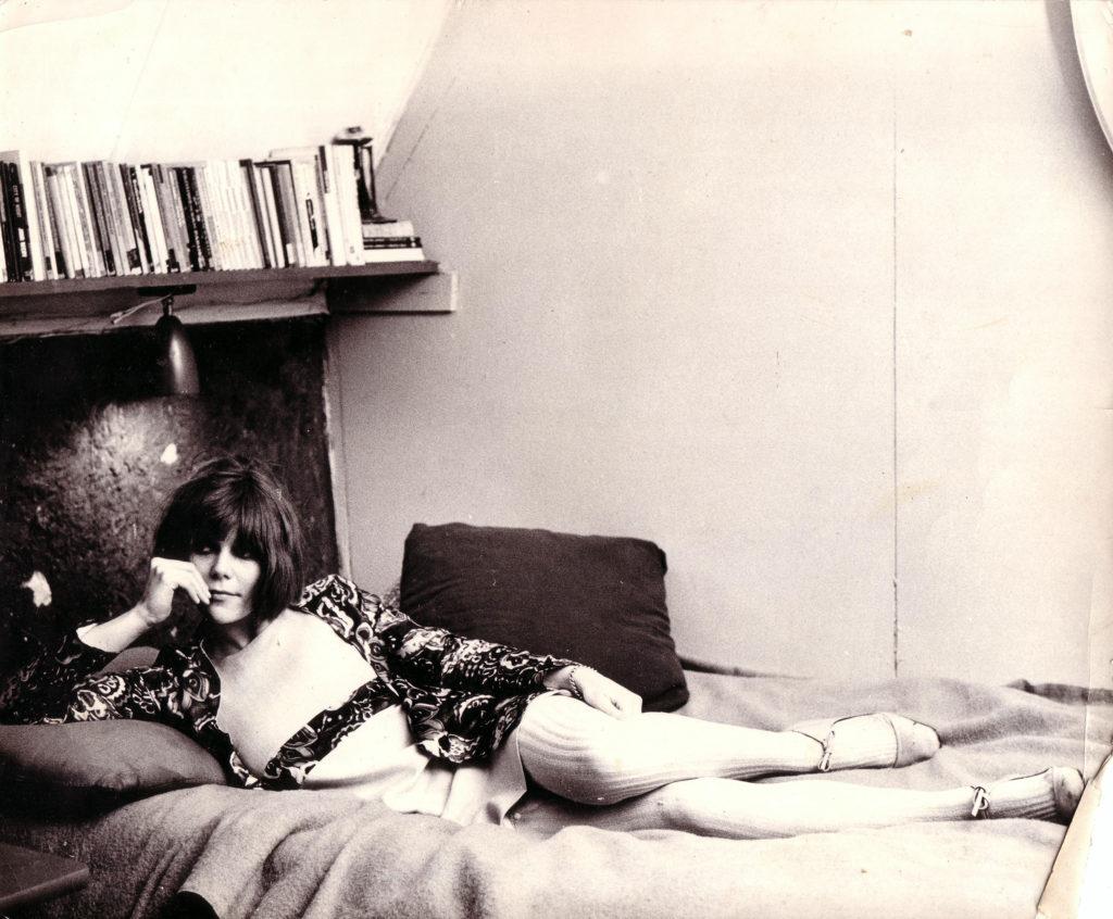 Een foto van een jonge Mila Jansen die in een erotische pose op een bed ligt. Het is een stilstaand filmbeeld uit de film Deterioration of the Swieps Family, die in 1967 werd uitgebracht.