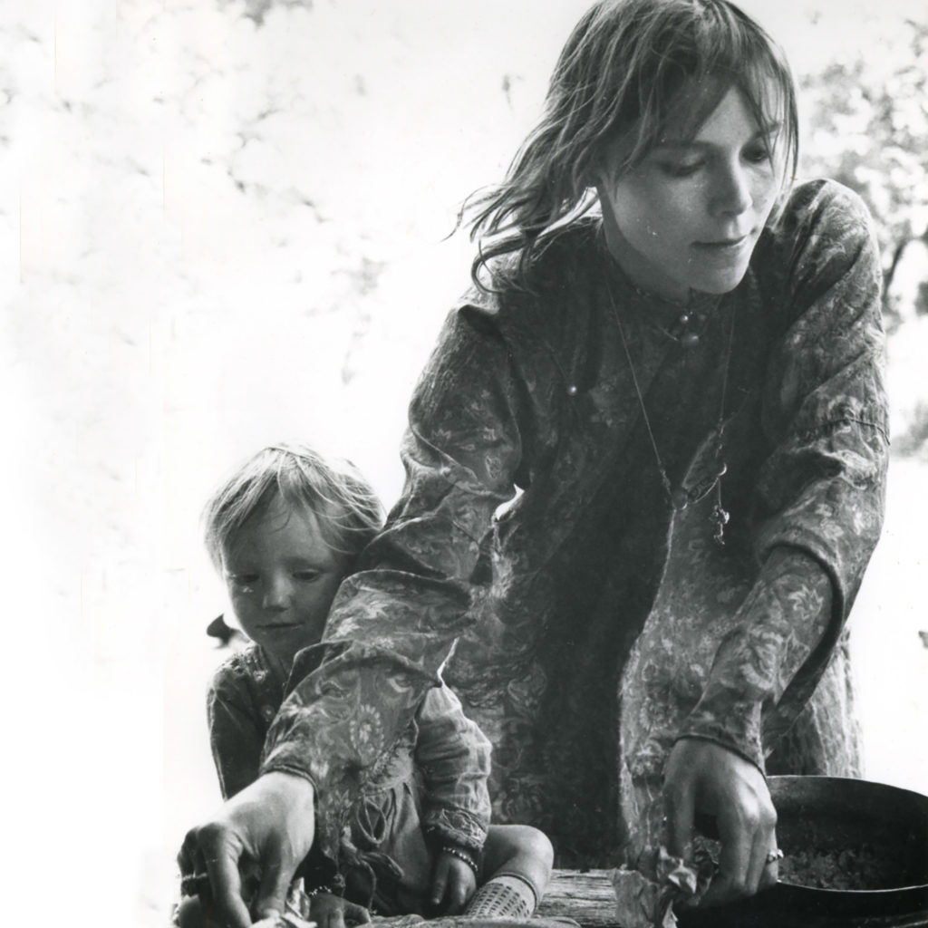 Photograph of Mila Jansen and her daughter Miloes. Mila is cooking, while Miloes is watching timidly. Both are wearing thin white dresses. The picture was taken in the North Indian town of Manali in 1968.
