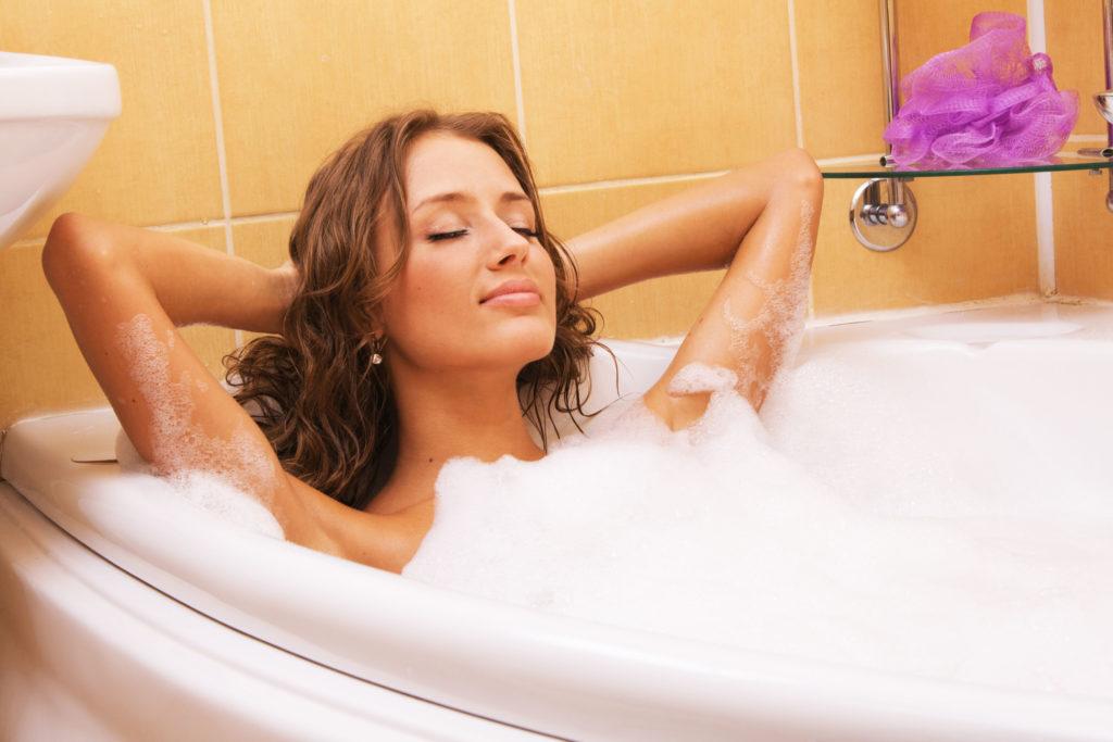 Foto einer jungen Frau, die in einer Badewanne entspannt.
