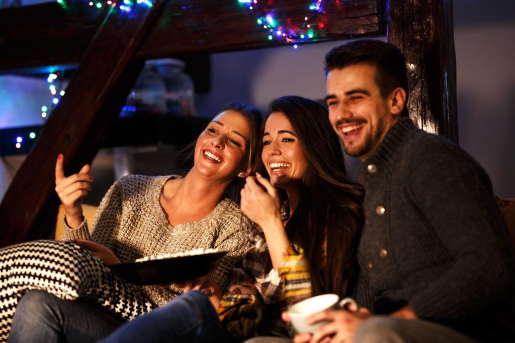 Foto van drie mensen die zich op een feestje amuseren en lachend dezelfde kant op kijken.