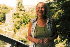 Foto de la leyenda del cannabis Mila Jansen, tomada en el Jardín Botánico de Ámsterdam en 2018. Mila lleva una camiseta verde con una blusa sin mangas, y sonríe a la cámara.
