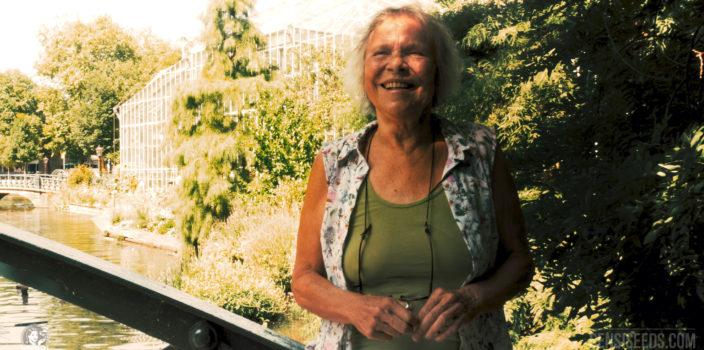 Foto der Cannabislegende Mila Jansen, das im Jahr 2018 im Botanischen Garten von Amsterdam entstanden ist. Mila trägt ein grünes Shirt und eine Bluse und lacht in die Kamera.
