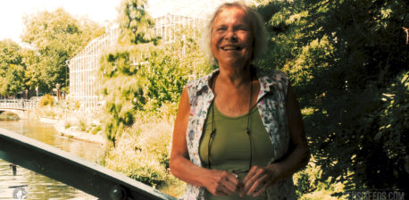 Photograph of cannabis legend Mila Jansen that was taken in the Amsterdam Botanical Gardens in 2018. Mila is wearing a green T-shirt and a blouse and is smiling at the camera.