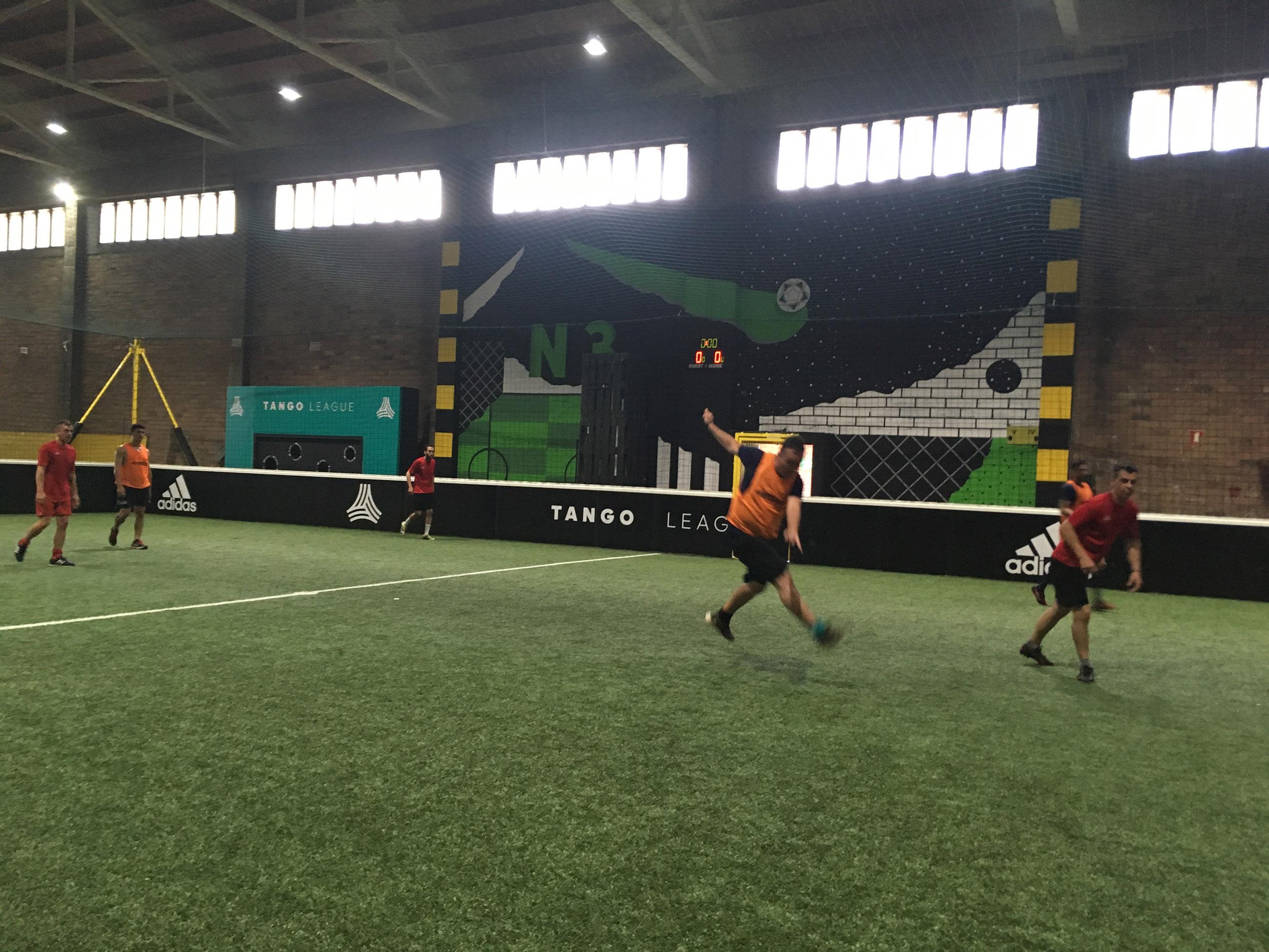 Een foto van een voetbalwedstrijd van de Mary Jane Football League. De wedstrijd wordt op een overdekt veld gespeeld. Er staan in totaal vijf spelers op het veld.