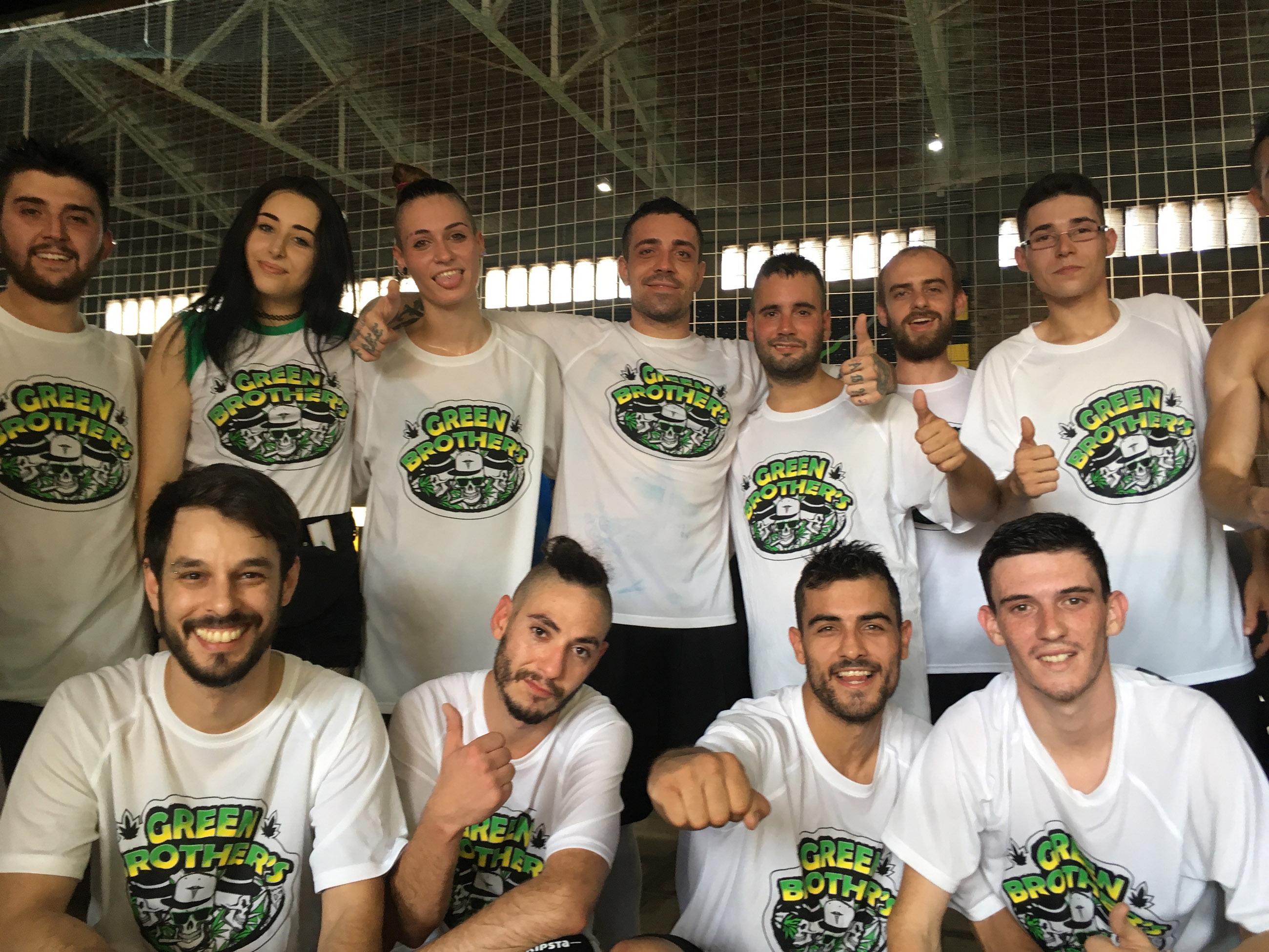 Foto der Green Brothers, das im Rahmen der Mary Jane Football League aufgenommen wurde. Anders als der Name vermuten lässt, sind auch Frauen Teil des Teams. Die elf Spieler und Spielerinnen tragen weiße T-Shirts der Cannabis Dispensary Green Brothers, die sich in Barcelona befindet.