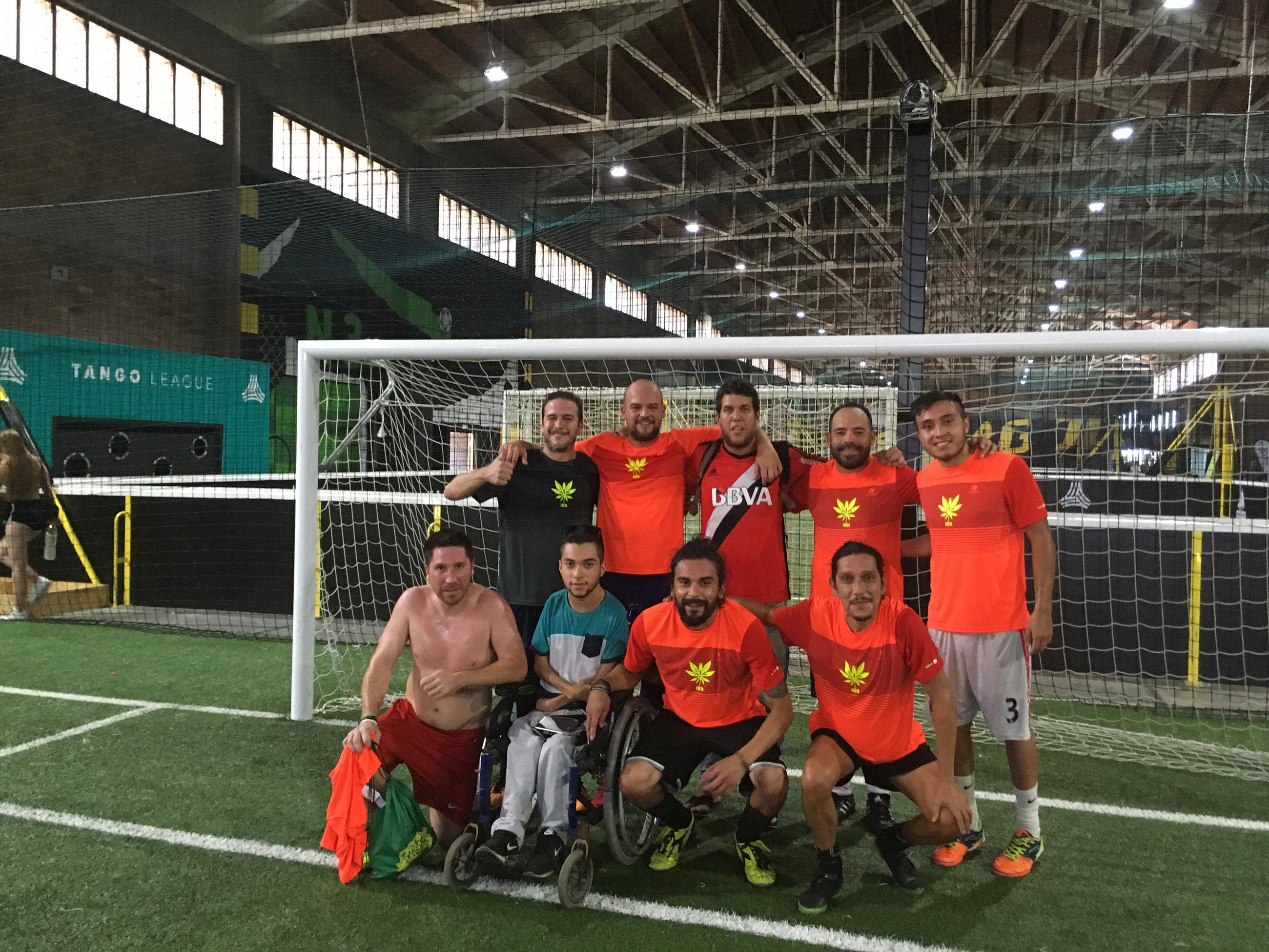 Op de foto staat het voetbalteam van de Spaanse Freya Cannabis Club. Er zijn zeven mannen in oranje voetbalshirts te zien, die op een overdekt voetbalveld voor het doel staan.