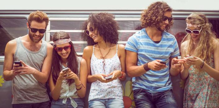 Foto van een groep relaxte, aantrekkelijke jonge mensen die voor een camperbusje staan en op hun telefoon kijken. Ze lachen en dragen allemaal zonnebrillen.