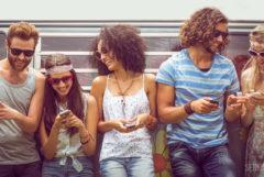 Foto einer Gruppe von hippen, jungen Menschen, die vor einem Campingbus stehen und in ihre Mobiltelefone gucken. Sie lachen und tragen Sonnenbrillen.