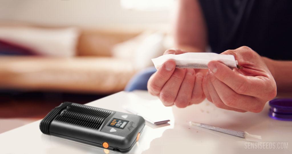 Imagen de interior. Sobre la mesa se ve un porro y un vaporizador para fumar cannabis. Se ven también dos manos, enrollando un porro justo encima de la superficie de la mesa.