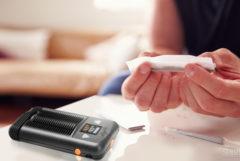 Een foto die binnen is genomen. Op de tafel liggen een joint en een vaporizer voor het roken van cannabis. Je ziet ook twee handen die vlak boven het tafelblad een joint rollen.