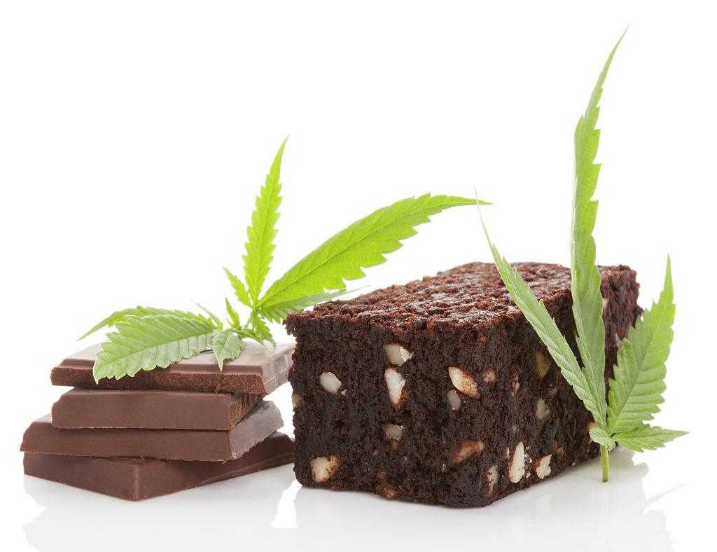 Links op de foto ligt een stapeltje vierkante chocolaatjes, met rechts daarvan een brownie. Een paar groene cannabisbladeren versieren het tafereel.