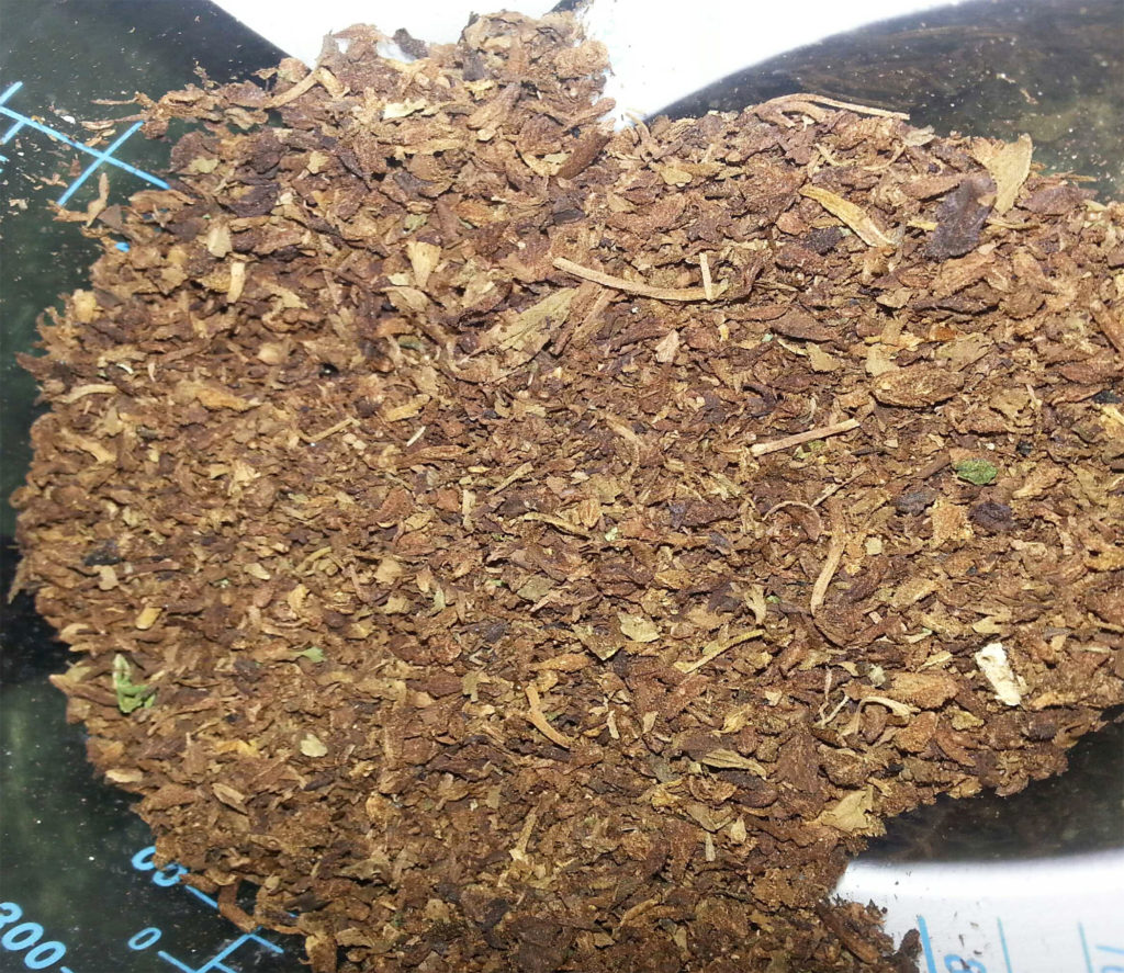 A close-up of vaporized cannabis, which is greenish-brown in colour, and looks very dry.
