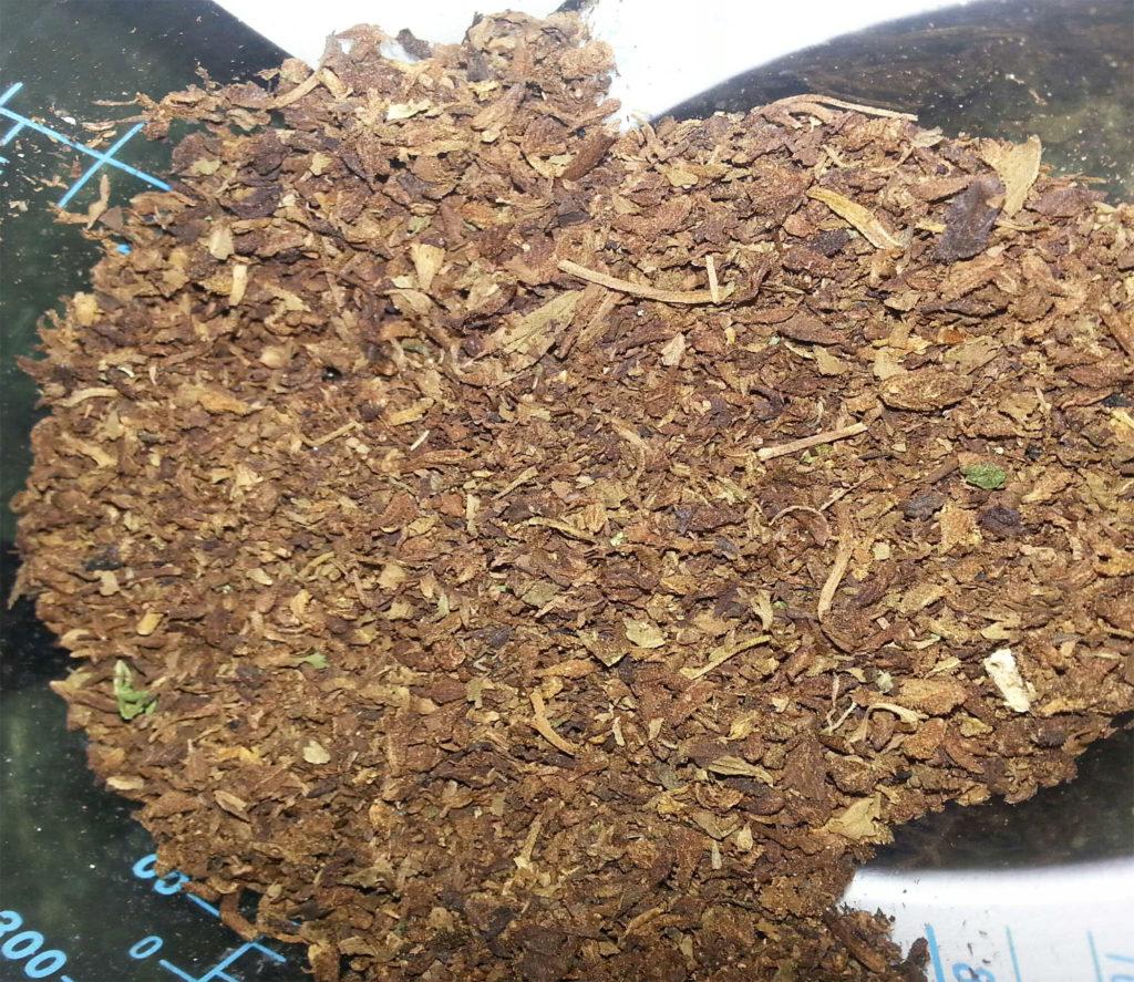 Een close-up van gevaporiseerde cannabis, die een groenbruine kleur heeft en er erg droog uitziet.