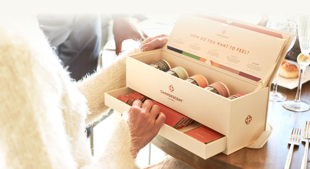 Photo of an elegant wooden box from Canndescent, displaying a number of different cannabis strains. On the box it says 'How do you want to feel?'A woman is looking at the contents of the box.