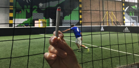 Auf dem Foto ist ein Indoor-Fußballplatz mit einem Spieler in Blau zu sehen. Davor befindet sich ein schwarzes Netz und eine Hand, die einen glühenden Joint ins Bild hält. Unten rechts befindet sich das Logo von Sensi Seeds.