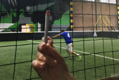 La photographie montre un terrain de foot en salle avec un joueur habillé en bleu. On voit, à l'avant-plan, un filet noir et une main qui tient un joint incandescent. Le logo Sensi Seeds est visible en bas à droite.