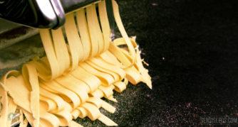 Foto van een pastamachine waarmee gele henneptagliatelle wordt gesneden.