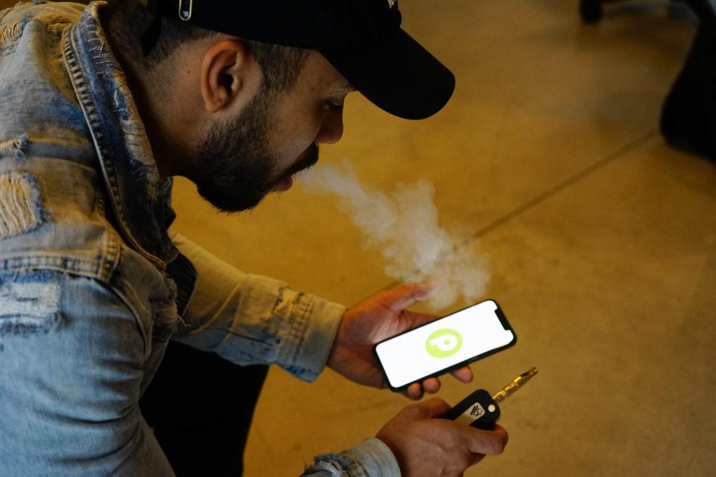 Photo d'un jeune homme en train de se connecter sur une appli de rencontre destinée aux consommateurs de cannabis. Il tient un téléphone portable dans la main gauche et un vaporisateur dans la main droite.