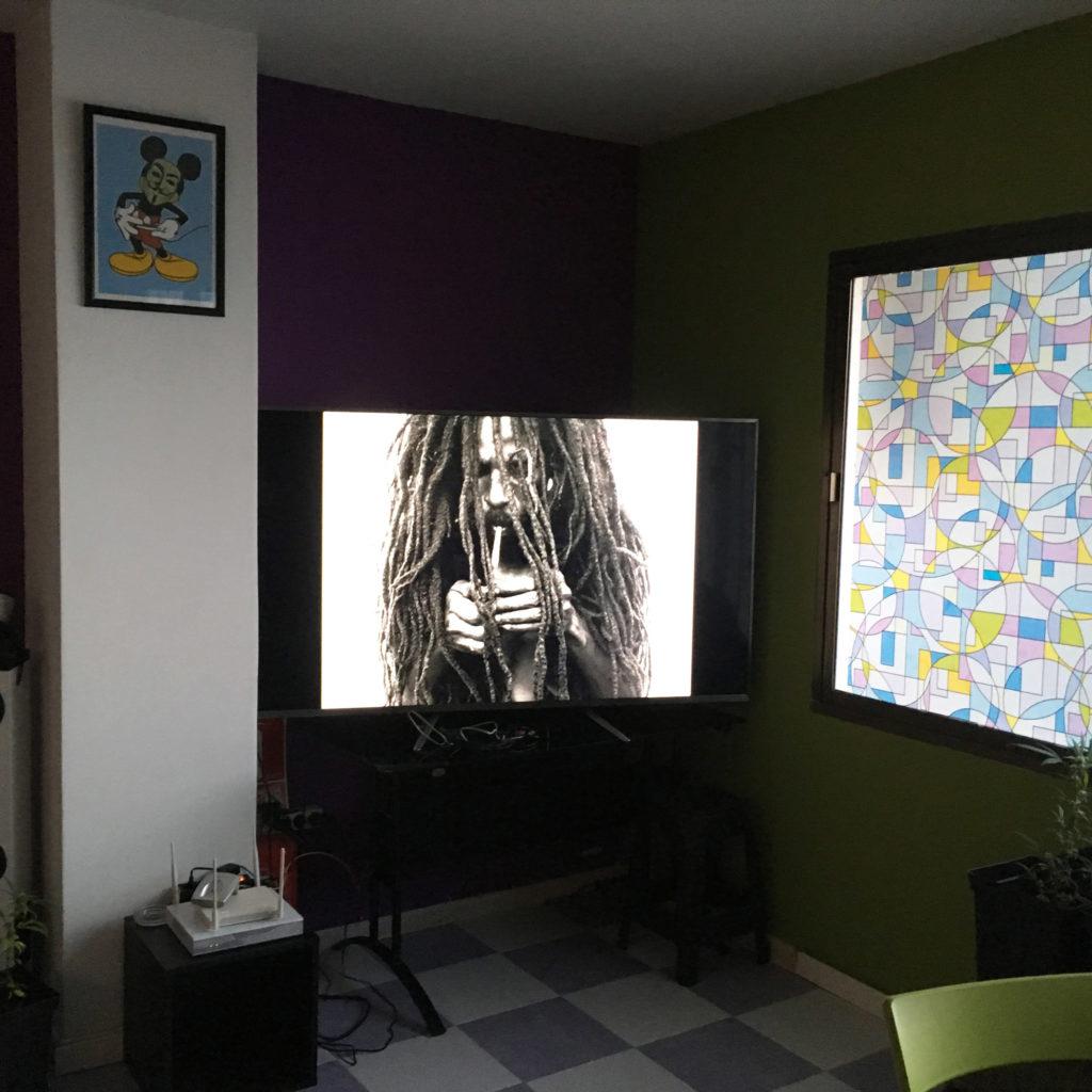Photo d'une pièce mal éclairée avec deux posters encadrés et un écran télé montrant un homme avec des dreadlocks en train d'allumer un joint.