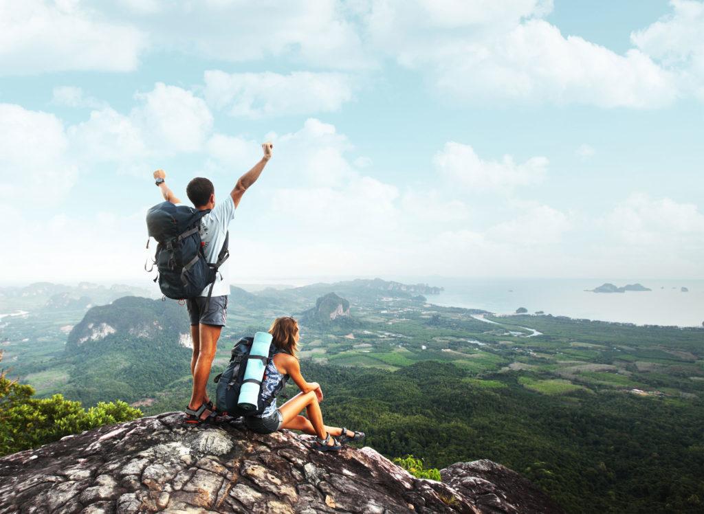 Foto von zwei jungen Menschen mit Rucksäcken, das auf einer Bergspitze oder einem Kliff aufgenommen wurde. Während der Mann die Arme in die Luft reißt, sitzt die Frau ruhig daneben. Die Aussicht auf die grüne Natur und das Meer ist atemberaubend.