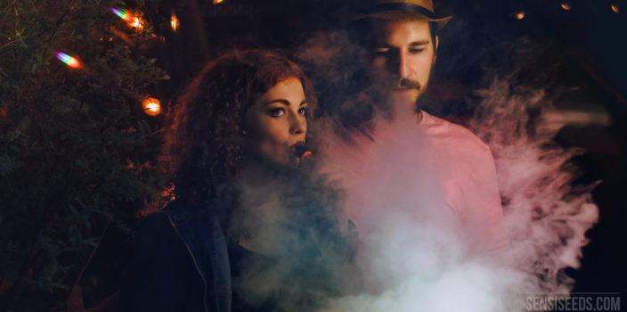 Foto van een jonge man en een jonge vrouw. De foto is 's nachts genomen. De vrouw inhaleert uit een vaporiser die grote rookwolken produceert.